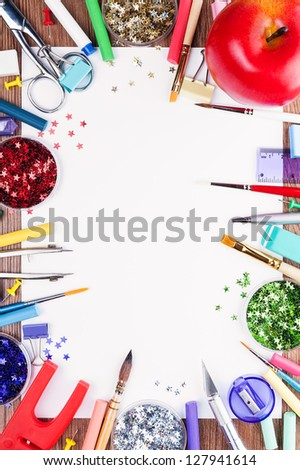 All the decorating and painting. White sheet of paper, surrounded by tools for drawing, dotted with decorative stars and big red apple. - stock photo