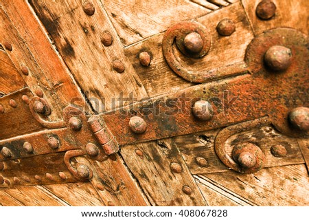 All the glamour is gone; Detailed view of neglected wooden door with rusty iron door fittings; Metalwork at grunge wooden door - stock photo