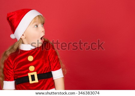 All these for me! Profile of a little cute girl wearing Christmas hat and Santa outfit looking away shocked with her mouth open copyspace on the side - stock photo