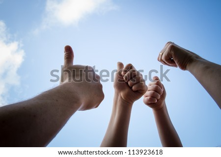 All thumbs up on cloudy sky in the background - stock photo