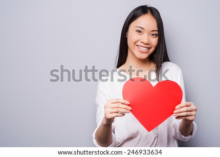 All we need is love! Beautiful young Asian woman holding big heart shaped valentine card and smiling while standing against grey background   - stock photo