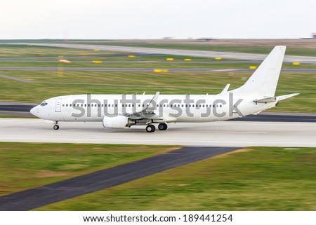 All white plane on the airport runway - stock photo