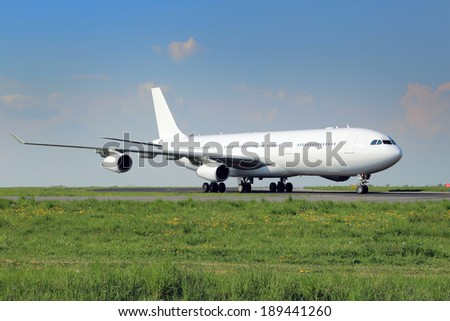 All white plane taxiing on the airport taxiway - stock photo