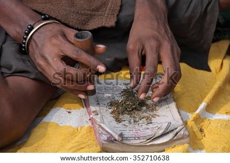 ALLAHABAD, INDIA - FEBRUARY 07, 2013: Sadhu is preparing his chillum to smoke ganja (marihuana)   - stock photo