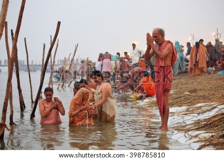 ALLAHABAD, INDIA - FEBRUARY 12, 2013: Thousands of Hindu devotees come to confluence of the Ganges and Yamuna River for holy dip during the festival Kumbh Mela. The world's largest religious gathering - stock photo