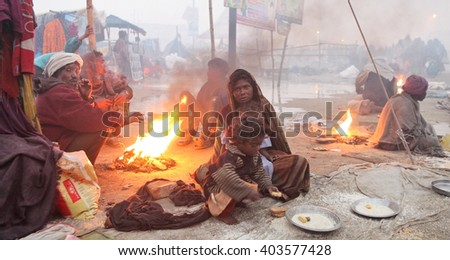 ALLAHABAD, UTTAR PRADESH, INDIA - FEBRUARY 11, 2013: unidentified poor Indian beggar family is warming oneself at the fire at Maha Kumbh Mela festival. - stock photo