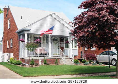 ALLEN PARK, MI-JUNE, 2015:  Typical 1950's suburban house with a flag on the porch. - stock photo