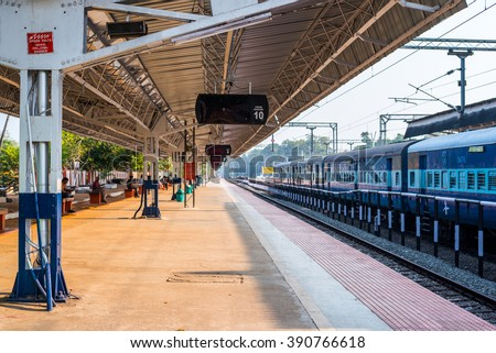 ALLEPPEY, INDIA - FEBRUARY 7: Empty platform under a shed and a train at the Alleppey railway station on February 7, 2016 in Alleppey, India. - stock photo