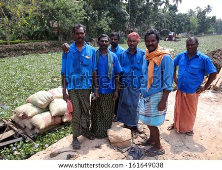ALLEPPEY, INDIA - MARCH 2013: workers at Kerala Backwaters, people transporting grain sacks - stock photo