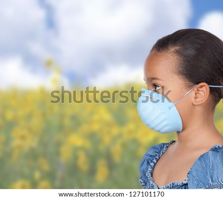 Allergic latin girl with a blue mask in a field with many flowers - stock photo