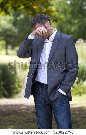 allergies - sick middle age businessman with itchy eyes removing his glasses for fatigue or hay fever allergies in park,natural summer daylight - stock photo