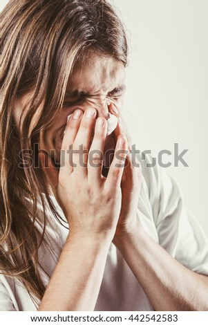 Allergy and cold concept. Young long haired sick man with hygienic tissue. Guy blowing nose.