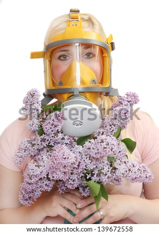 Allergy to pollen concept. Young woman in protection mask with bunch of flower. - stock photo