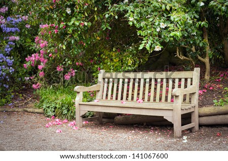Alley and old wooden bench in park. - stock photo