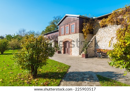 Alley in a park and view of traditional house in Tomaszowice village on sunny autumn day, Poland