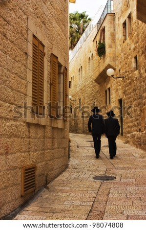 Alley in Jerusalem old city with two orthodox men walking away , Israel - stock photo