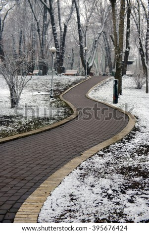 alley in snow-covered park - stock photo