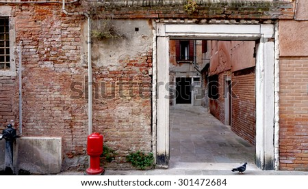 Alley with ancient brick wall building in Venice, Italy - stock photo
