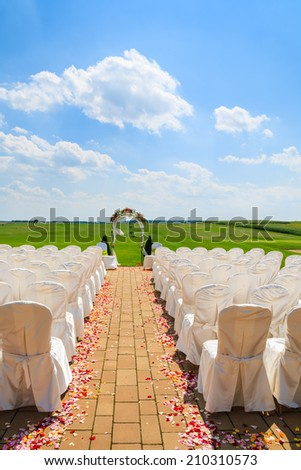 Alley with rows of white chairs in golf club prepared for weeding ceremony, Poland