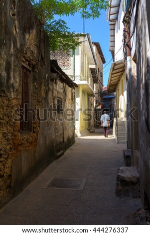 alleyway in Zanzibar city, stone-town, with a pedestrian walking through the thoroughfare