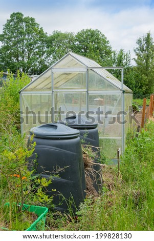 Allotment garden green house with compost bins - stock photo