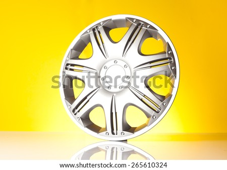 alloy wheel isolated on yellow background - stock photo