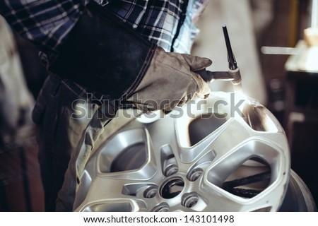 Alloy wheel repair, Welding alloy rim. - stock photo