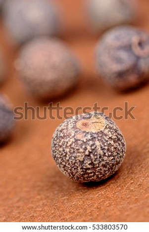 Allspice on brown background closeup