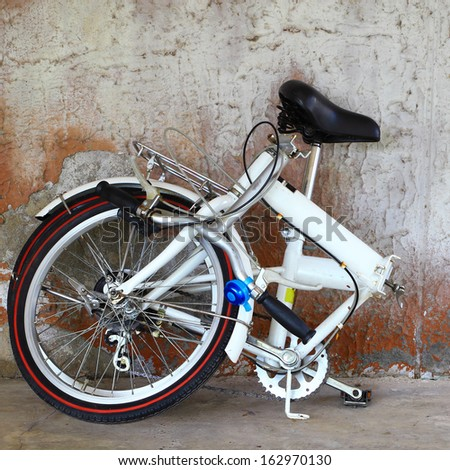 Alluminium folding bicycle  and old wall - stock photo