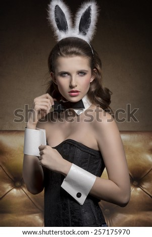 allure pin-up woman with funny easter bunny ears, sexy corset and papillon looking in camera with charming expression  - stock photo