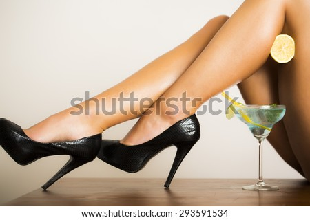 Alluring bare sexy female legs in black leather shoes on high heels with half fresh juicy orange and blue cocktail with green lime in glass on white background, horizontal picture - stock photo