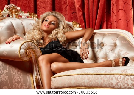 alluring blond relaxing on a sofa in luxury interior - stock photo