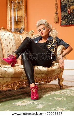 alluring blond sitting on a sofa in luxury interior