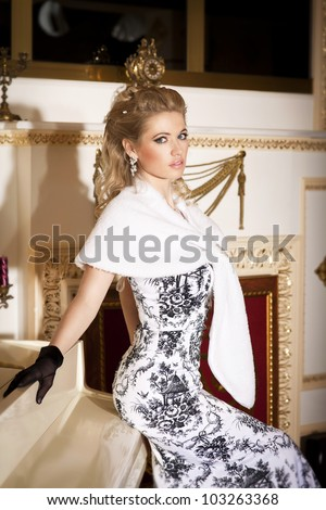 alluring blond woman pianist with grand piano in luxury hotel. Stylish rich slim girl in gloves elegant dress and fur with healthy glossy hair at villa apartment. Lady musician with diamond jewelry - stock photo