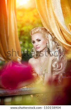 alluring blond woman relaxing in luxury interior.Stylish rich slim girl in sexy golden dress with long glossy curly hair at hotel villa apartment.Fashion glamour shot at vacation resort autumn.series - stock photo