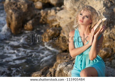 Alluring blonde woman with big seashell in Greek Goddess style at sunset. Beautiful girl in blue silk luxury dress with golden jewelry. freedom and romantic concept. positively thinking, Sea Nymph. - stock photo