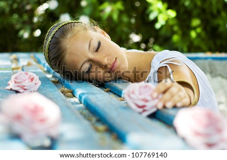Alluring brown-haired woman outdoor in Greek goddess style lying on the bench with closed eyes. stylish romantic girl holding a pink rose. romantic concept. Amazing Nymph. Greece - stock photo