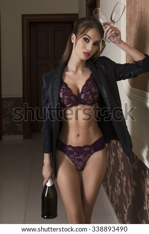 alluring brunette woman posing with lingerie and open jacket, taking bottle of champagne and glasses in the hands, ready for very sexy new year night toast  - stock photo
