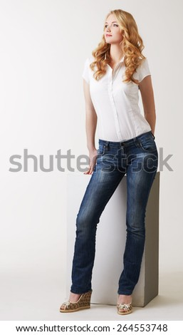 Alluring model posing in classic blouse and jeans - stock photo
