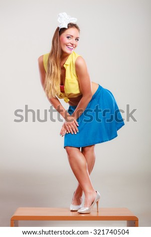 Alluring seductive pretty pin up girl wearing hairband bow, skirt and high heels. Attractive gorgeous young retro woman dancing on table. - stock photo