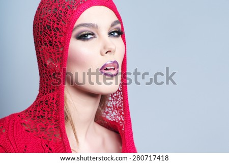 Alluring sexual young woman in red knitted jacket with bright make up and beautiful slim body looking forward standing on grey wall background copy space, horizontal picture - stock photo