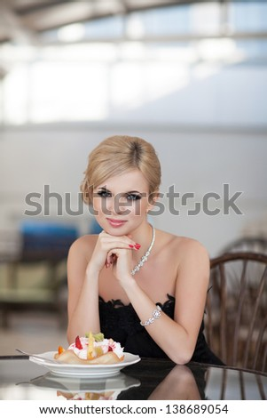 Alluring sexy blonde woman in restaurant cafe with ice cream tiramisu cake beautiful girl in black dress hairstyle and makeup eating dessert. Beauty fashion slim model rich retro lady in vintage dress - stock photo
