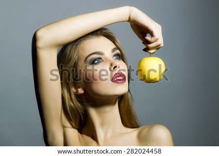 Alluring sexy girl with bright make up looking away holding fresh yellow apple standing on gray background copyspace, horizontal picture - stock photo