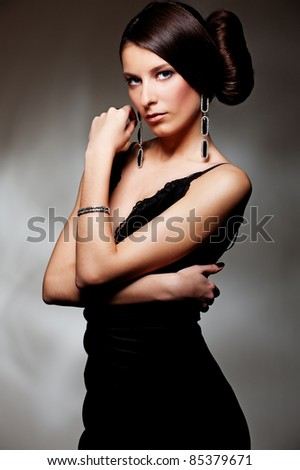 alluring sexy woman in evening dress posing over dark background - stock photo