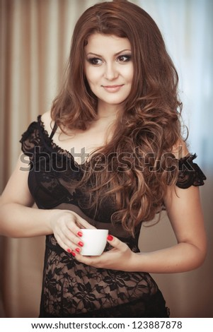 Alluring woman in sexy lingerie at home with coffee at morning. Brunet girl with gorgeous long hair bright makeup and hairstyle in erotic wear holding a cup of hot aroma espresso. tonality - stock photo