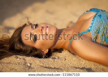 alluring woman relaxing on sand beach in swimwear smiling and fiel happy.Beautiful slim girl resting and enjoying sun at vacation. arabian belly dancer oriental professional artist in carnival costume