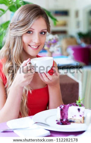 alluring young woman drinking tea and smiling. shot in cafe - stock photo