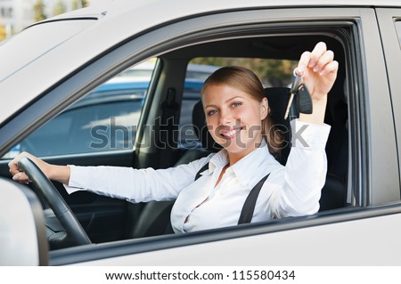 alluring young woman sitting in car and showing the car keys - stock photo