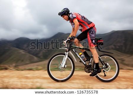 "ALMATY, KAZAKHSTAN - APRIL 30: A.Litvinov (N40) in action at Adventure mountain bike cross-country marathon in mountains ""Jeyran Trophy 2011"" April 30, 2011 in Almaty, Kazakhstan. - stock photo"