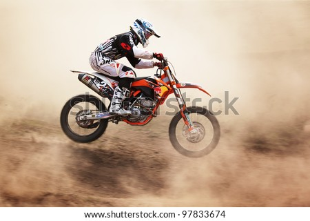 "ALMATY, KAZAKHSTAN - APRIL 10: A.Simonenko(1) flies through the air at the Motocross competition ""Fabrichny Cup""- Open Championship of Kazakhstan on April 10, 2011 in Kargaly, Kazakhstan. - stock photo"